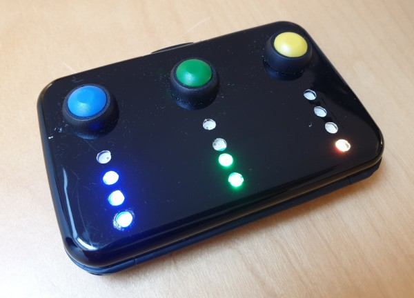 Picture showing the finished timer: a small, black business card case with three buttons (blue, green, yellow) and three strips with 4 neopixels each.